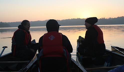 3 studerende i kano ved solnedgang
